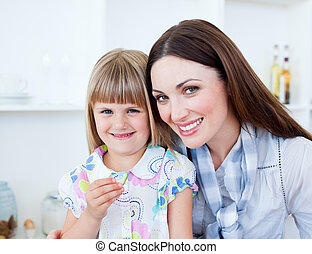 Caring mother and her daughter eating vegetables