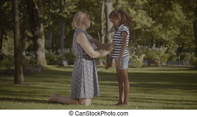 Caring mother comforting her sad daughter in park
