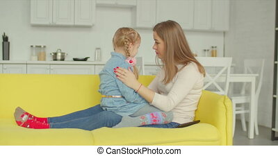 Caring mother consoling her upset daughter on sofa - Caring...