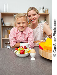 Caring mother eating fruit with her daughter