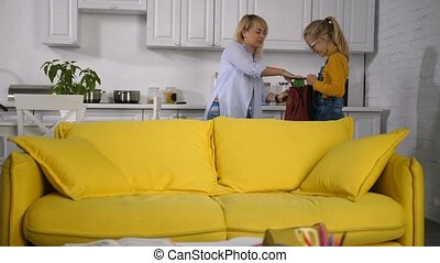 Caring mother giving school lunchbox to girl