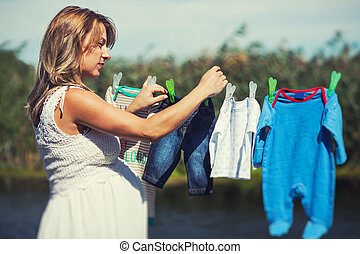 Caring mother hanging baby clothes on a string