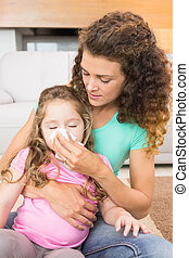 Caring mother helping her little daughter blow her nose
