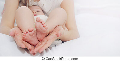caring mother holding in hands little foots of her cute baby boy