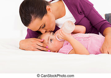caring mother kissing baby daughter