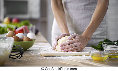 Caring mother kneading the dough at the kitchen, woman making cakes, top-view