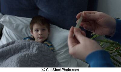 Caring mother measuring temperature of sick boy