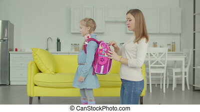 Caring mother packing backpack of schoolgirl at home -...