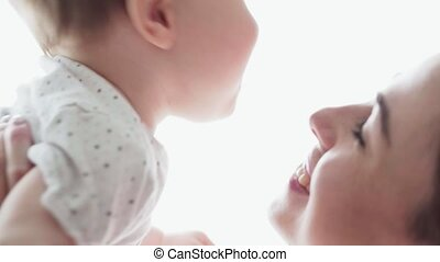 Caring mother playing with happy little baby, kisses and smiles