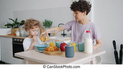 Caring mother putting cereal in childs bowl in kitchen at...