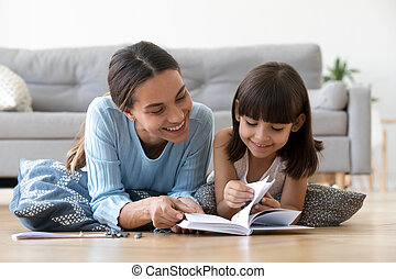 Caring mother reading book with little kid girl at home