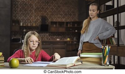 Caring mother scolding her daughter for bad grades