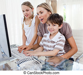 Caring mother teaching her children how to use a computer