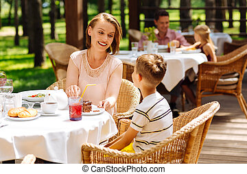Caring mother treating her son with croissants and tea