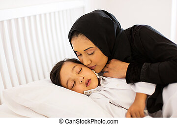 muslim mother kissing baby boy - caring muslim mother...