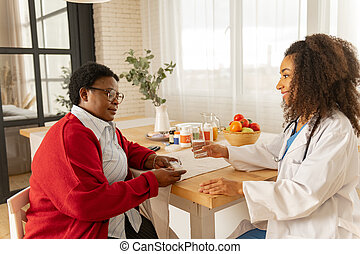 Caring nurse giving pills and glass of water to aged woman