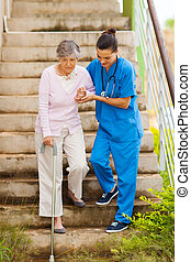 caring nurse helping senior patient walking down stairs