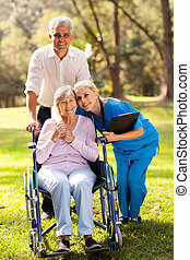 caring nurse hugging senior patient