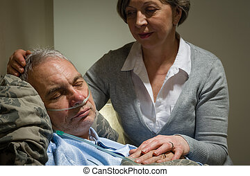 Caring nurse with sleeping senior male patient - Caring...