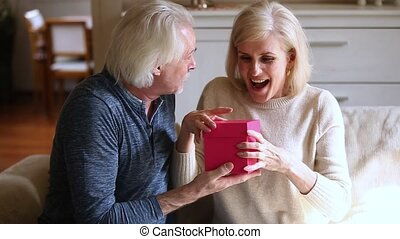 Caring old husband giving gift box to excited mature wife