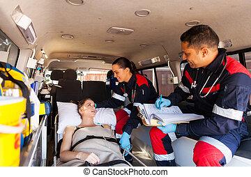 paramedics talking to patient on ambulance