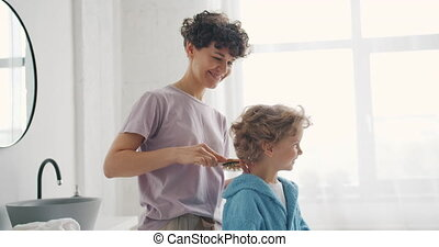 Caring parent brushing small boy's hair with hairbrush in...