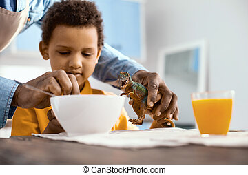Caring parent helping his little son feed toy dinosaur