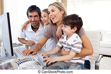 Caring parents teaching their children how to use a computer...