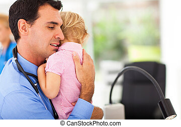 caring pediatrician hugging a sick baby