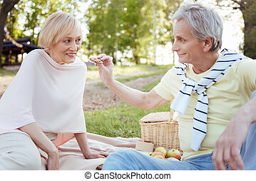 Caring pensioners having picnic in the park
