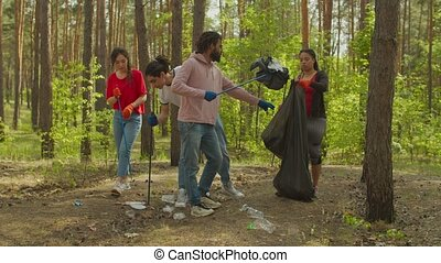 Caring people picking up plastic trash in wood - Team of ...