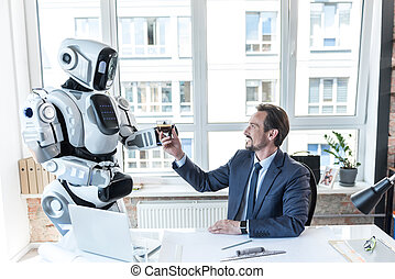 Caring robot is giving espresso to businessman