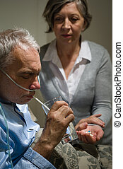 Caring senior wife holding drugs for husband
