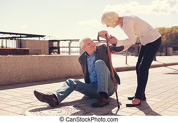 Caring senior woman helping her husband get up