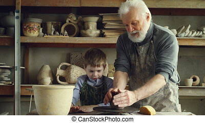 Caring silver-haired grandfather is teaching young cute...