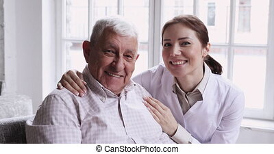 Caring smiling female caregiver embracing happy senior ...