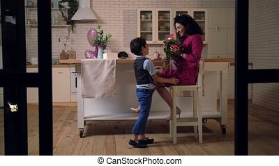 Caring son bringing bouquet of flowers to mother - Joyful...