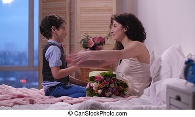 Caring son presenting flowers to mother in bed - Cute arab...
