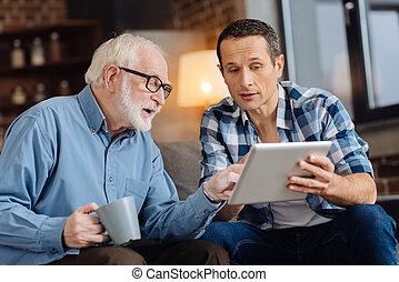 Caring son showing interesting article on tablet to his father