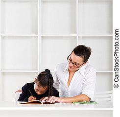 caring tutor helping schoolgirl