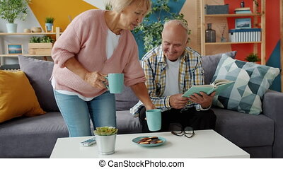 Caring wife bringing tea and cookies to husband reading book enjoying snack at home