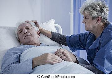 Caring wife comforting elderly husband