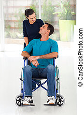 caring wife talking to disabled husband