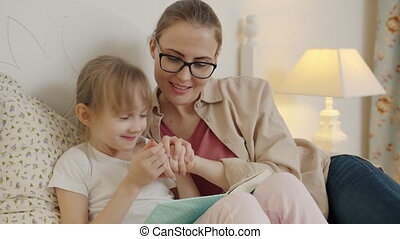 Caring woman and pretty little girl reading book in bed ...