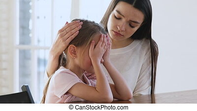 Caring worried young mum comforting sad crying child daughter