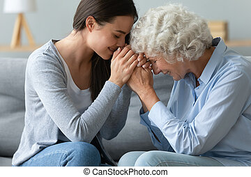 Caring young adult woman granddaughter hold hands of old grandmother