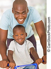 young african father pushing son on a bike