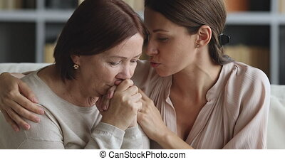 Caring young daughter apologizing comforting sad old mother ...