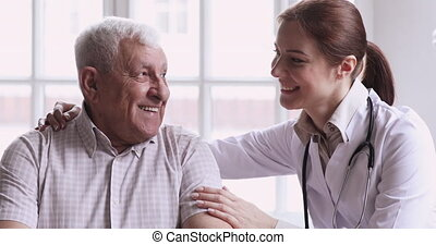 Caring young female doctor caretaker help support happy senior man