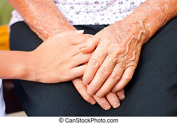 Caring - Young hands between elderly ones.